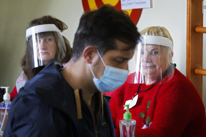 Members of the election commission wearing face masks to protect against coronavirus infection, look at a voterat a poling station during Leningrad region's governor and municipal elections in Luppolovo village, outside St. Petersburg, Russia, Sunday, Sept. 13, 2020. Leningrad region is the territory surrounding St. Petersburg. Elections are being held to choose governors and legislators in about half of Russia's regions. (AP Photo/Dmitri Lovetsky)