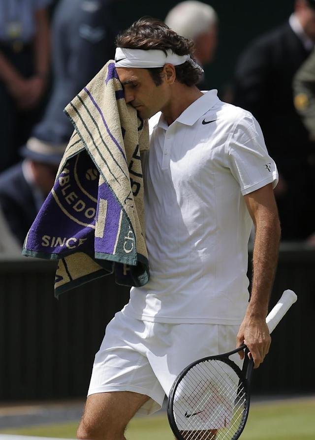 Roger Federer of Switzerland wipes his face with a towel during the men's singles final against Novak Djokovic of Serbia at the All England Lawn Tennis Championships in Wimbledon, London, Sunday, July 6, 2014. (AP Photo/Pavel Golovkin)