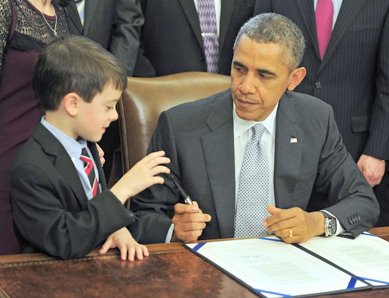 Obama presents a pen to Jacob Miller after signing legislation. (Photo: Pool via Getty Images)