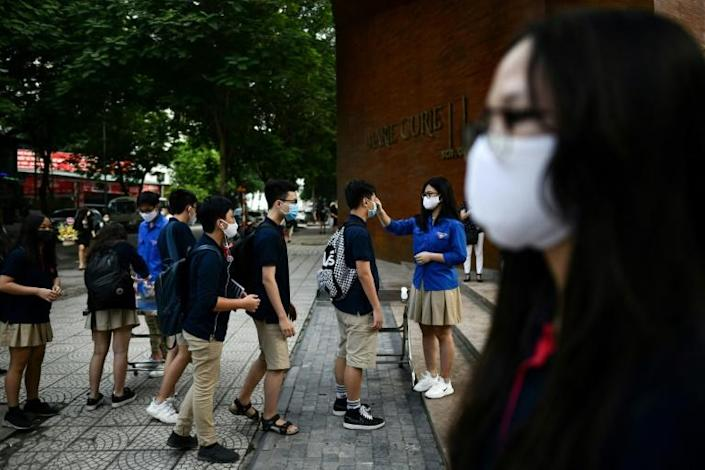 Students wearing face masks stand in a queue to get their temperatures checked in Hanoi (AFP Photo/Manan VATSYAYANA)