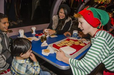 this happy elf is serving cocoa and cookies on the train to christmas town in - Train To Christmas Town