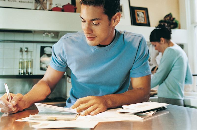 Young man paying bills from a checkbook.