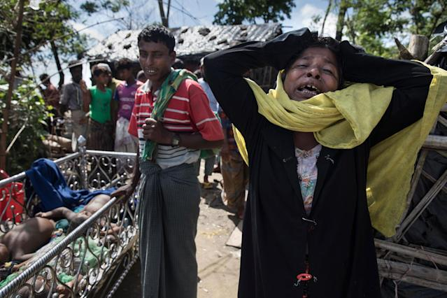 <p>Madia Khatun, a relative, grieves next to the bodies of 5 children, after an overcrowded boat carrying Rohingya fleeing Myanmar capsized overnight killed around 12 people including five children on October 9, on Shah Porir Dwip Island, Cox's Bazar, Bangladesh. (Photograph by Paula Bronstein/Getty Images) </p>