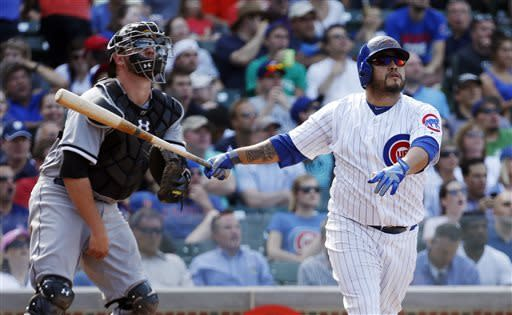 Chicago Cubs' Dioner Navarro, right, watches his three-run home run along with Chicago White Sox catcher Tyler Flowers during the seventh inning of a interleague baseball game Wednesday, May 29, 2013, in Chicago. It was Navarro's third home run of the game. (AP Photo/Charles Rex Arbogast)