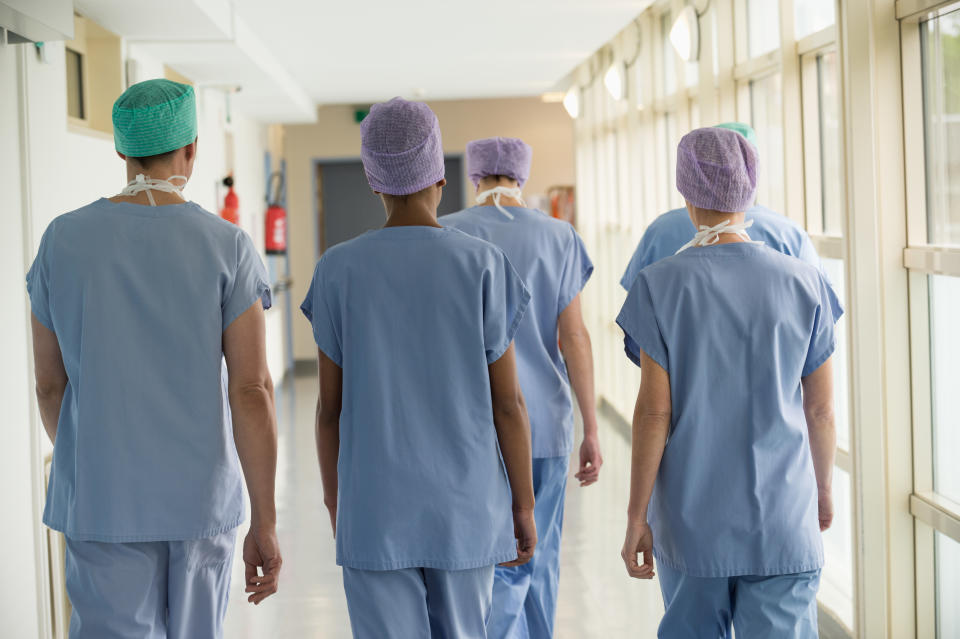 Rear view of a medical team walking in the corridor of a hospital