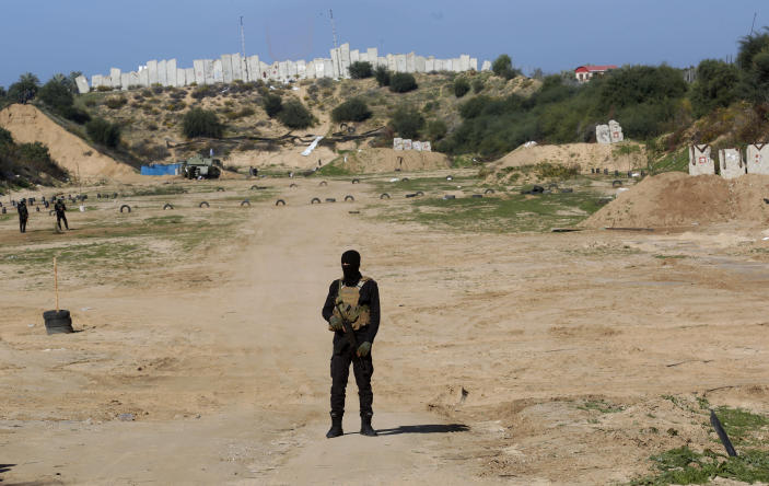 A Palestinian militant stands guard during a military drill organized by military factions outside Gaza City, Tuesday, Dec. 29, 2020. Palestinian militants in the Gaza Strip fired a salvo of rockets into the Mediterranean Sea on Tuesday as part of a self-styled military drill aimed at preparing for a possible war with Israel. (AP Photo/Adel Hana)