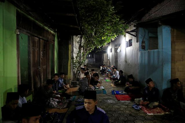 <p>Students sit outside as they learn Islamic scriptures in the evening during the holy month of Ramadan at Lirboyo Islamic boarding school in Kediri, Indonesia, May 24, 2018. (Photo: Beawiharta/Reuters) </p>