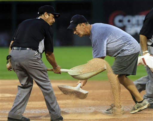 Chicago White Sox assistant groundskeeper Jose Diaz, left, and head groundskeeper Roger Bossard spread a drying agent during the seventh inning of a baseball game between the White Sox and Seattle Mariners, Sunday, Aug. 26, 2012, in Chicago. (AP Photo/John Smierciak)