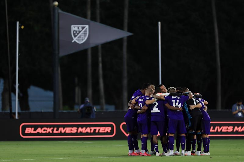 A group of MLS players huddles during an MLS is Back Tournament game.