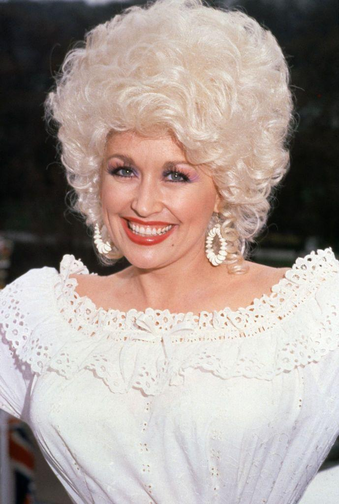 <p>Throughout the '70s, Parton's style was relatively laid-back and, well, toned down. She always put a feminine touch on everything she wore, and this lacy blouse echoes her country roots in a chic way at an early '80s press event in London. </p>