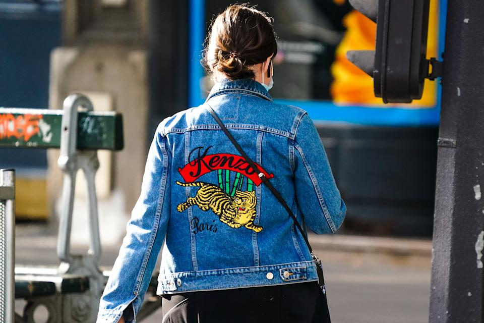 PARIS, FRANCE - JULY 02: A passerby wears a Kenzo blue denim jacket with a yellow printed tiger, on July 02, 2020 in Paris, France. (Photo by Edward Berthelot/Getty Images)