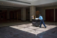 In this June 29, 2021, photo a work walks in the empty U.S. Capitol Visitor Center, closed since the COVID-19 shutdown in early 2020, is seen at the Capitol in Washington. (AP Photo/J. Scott Applewhite)