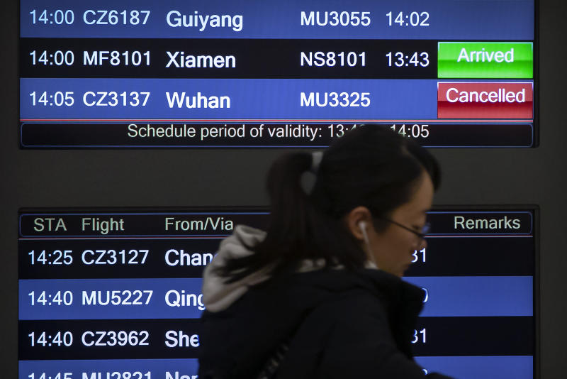 A traveler walks past a display board showing of arriving flights a canceled flight from Wuhan at Beijing Capital International Airport in Beijing, Thursday, Jan. 23, 2020. China closed off a city of more than 11 million people Thursday in an unprecedented effort to try to contain a deadly new viral illness that has sickened hundreds and spread to other cities and countries in the Lunar New Year travel rush. (AP Photo/Mark Schiefelbein)