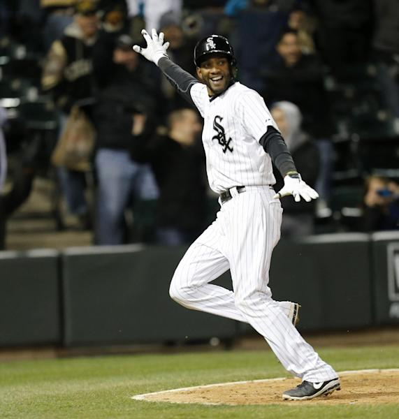 Chicago White Sox's Alexei Ramirez looks back at Marcus Semien after Semien reached first on a throwing error by Boston Red Sox shortstop Xander Bogaerts, allowing Ramirez to score the willing run during the ninth inning of a baseball game Tuesday, April 15, 2014, in Chicago. Chicago won 2-1.(AP Photo/Charles Rex Arbogast)
