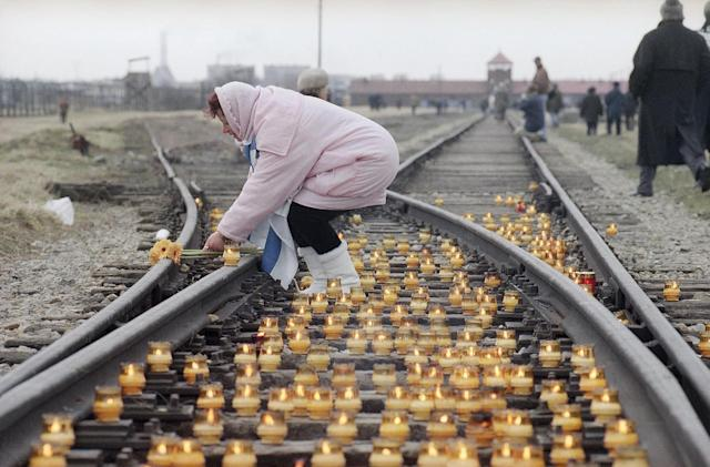 <p>A woman lights a candle on the rail tracks leading to the Nazi concentration camp of Auschwitz-Birkenau, Jan. 27, 1995, during the commemoration of the Soviet liberation of the camp 50 years ago. An estimated 1.5 million people were killed in the camp during Nazi rule. (Photo: Jacqueline Larma/AP) </p>