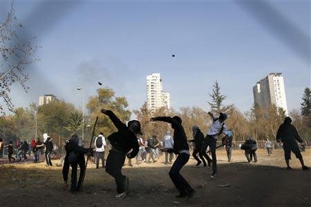 Student protesters throw stones against riot policemen (not pictured) during a demonstration to demand changes in the Chilean education system, in Santiago May 8, 2014. REUTERS/Ivan Alvarado