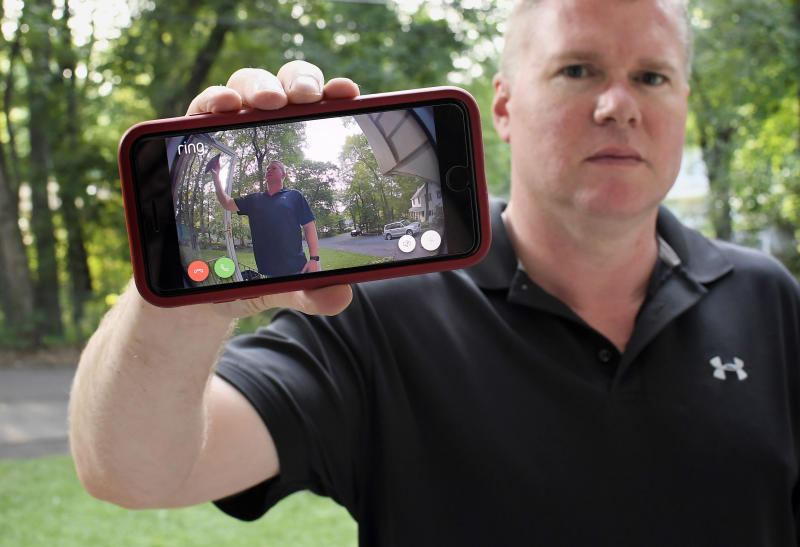 In this Tuesday, July 16, 2019, photo, Ernie Field holds up a live video of himself taken by a Ring doorbell camera at the front door at his home in Wolcott, Conn. Field won a free Ring camera and said he had to register for the app to qualify for the raffle. Now he gets alerts on his phone when a car drives by and a 30-second video when his daughter gets home from school. (AP Photo/Jessica Hill)