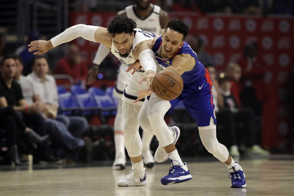 Los Angeles Clippers' Landry Shamet, right, works for a loose ball next to Memphis Grizzlies' Dillon Brooks during the first half of an NBA basketball game Saturday, Jan. 4, 2020, in Los Angeles. (AP Photo/Marcio Jose Sanchez)