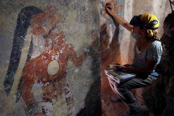 Conservator Angelyn Bass cleans and stabilizes the surface of a wall of a Maya house that dates to the ninth century. The figure of a man who may have been the town scribe appears on the wall to her left.