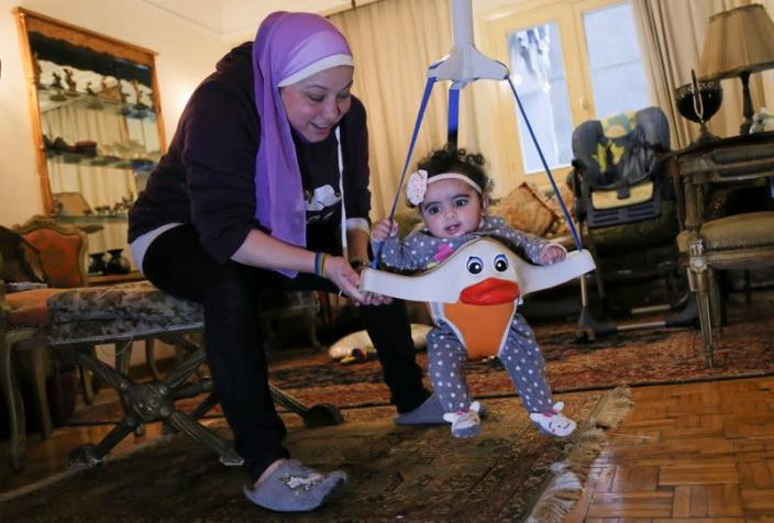 Yasmina al-Habbal, plays with Ghlaya, an orphan she sponsors, at her home in Cairo