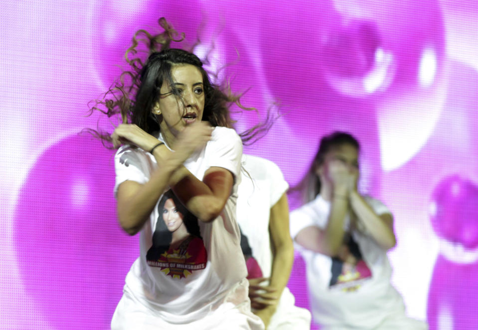 Dancers wearing t-shirts with a picture of TV star Kim Kardashian perform before her arrival in Riffa, Bahrain, Dec. 1, 2012. Just hours after reality TV star Kim Kardashian gushed about her impressions of Bahrain, riot police fired tear gas to disperse more than 50 hardline Islamic protesters denouncing her presence in the Gulf kingdom. (AP Photo/Hasan Jamali)