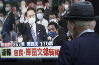 """A pedestrian looks at a public TV showing Fumio Kishida, former foreign minister, with a live broadcast of the Liberal Democratic Party (LDP}'s presidential election Wednesday, Sept. 29, 2021, in Tokyo. Kishida has won the governing party leadership election and is set to become the next prime minister. The Japanese letters read: """"Fumio Kishida new LDP president."""" (AP Photo/Eugene Hoshiko)"""
