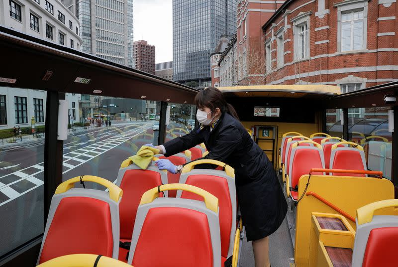 A tour guide of Hato Bus Co. disinfects seats of an open-top sightseeing bus, as the tour service resumed after Japan's government lifted the coronavirus disease (COVID-19) state of emergency in the Tokyo area