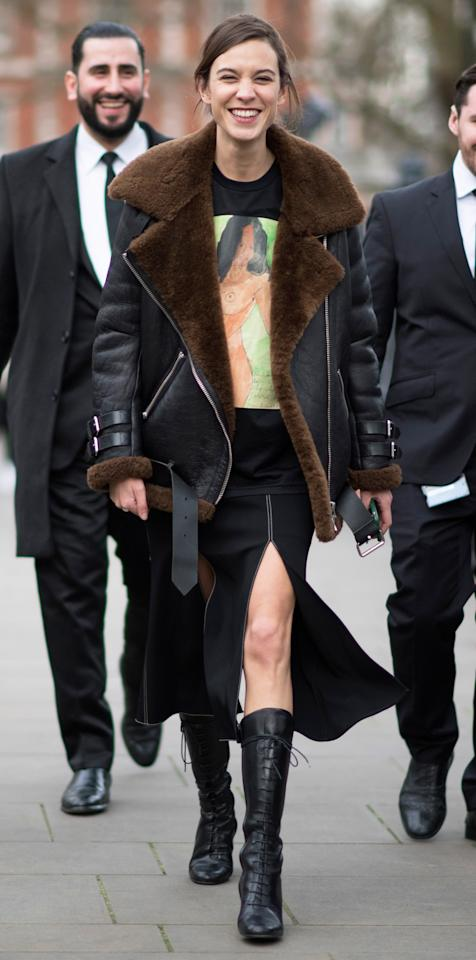 "<p>Chung kept warm during London Fashion Week in a shearling-lined coat (get a similar style <a rel=""nofollow"" href=""https://click.linksynergy.com/fs-bin/click?id=93xLBvPhAeE&subid=0&offerid=390098.1&type=10&tmpid=8157&RD_PARM1=http%253A%252F%252Fshop.nordstrom.com%252Fs%252Fbetsey-johnson-mixed-media-faux-shearling-jacket%252F4345148%253Forigin%253Dcategory-personalizedsort%2526fashioncolor%253DBLACK%25252F%252520CREAM&u1=ISAlexaChungStreetStyle3.22JA"">here</a>), black graphic tee, and lace-up boots, but still showed a little leg with a black, thigh-high slit skirt. </p>"