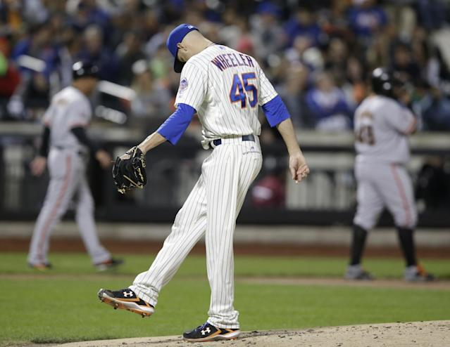 New York Mets starting pitcher Zack Wheeler (45) kicks at the mound as San Francisco Giants Pablo Sandoval, right, stands at third in the second inning of a baseball game Tuesday, Sept. 17, 2013, in New York. Wheeler allowed three runs in the inning. (AP Photo/Kathy Willens)