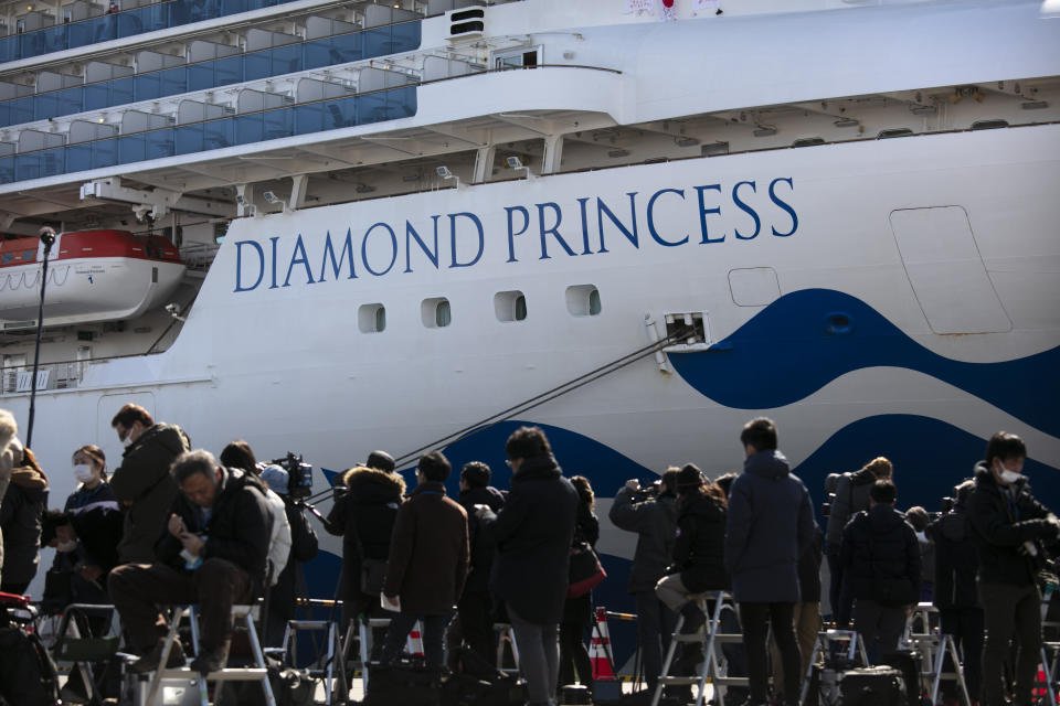 FILE - In this Feb. 11, 2020, file photo, media gather outside the quarantined Diamond Princess cruise ship in Yokohama, near Tokyo. Life on board the luxury cruise ship, which has dozens of cases of a new virus, can include fear, excitement and soul-crushing boredom, according to interviews by The Associated Press with passengers and a stream of tweets and YouTube videos. (AP Photo/Jae C. Hong, File)