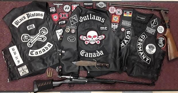 John Robert Berthiaume and Jennifer Lynn Chisholm faced multiple charges after police seized weapons and motorcycle gang gear from their Ben Eoin property in October 2020. (Cape Breton Regional Police/Facebook - image credit)