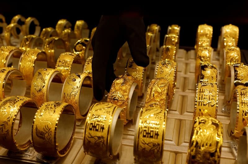 FILE PHOTO: A salesperson arranges 24K gold bracelets for Chinese weddings at Chow Tai Fook Jewellery store in Hong Kong