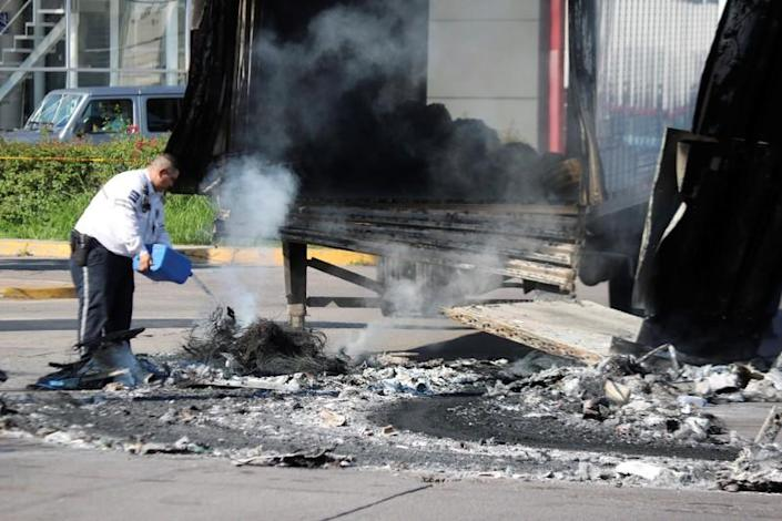 Police officer pours water on the burnt wreckage of a truck a day after cartel gunmen clashed with federal forces in Culiacan