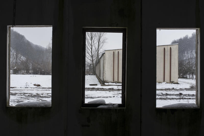 FILE- In this file photo dated Saturday, March 7, 2015, a now abandoned warehouse where over 1,000 Muslim Bosniak men and boys are known to have been killed in July 1995 in the village of Kravica on the outskirts of Srebrenica.  Eight former Bosnian Serb police officers were charged with participating in the killing of 1,313 Muslims in a warehouse in Kravica, but a Serbian appeals court on Thursday July 13, 2017, stopped the landmark trial because of legal procedural complaints which will force the trial to be restarted from scratch. (AP Photo/Sulejman Omerbasic, FILE)