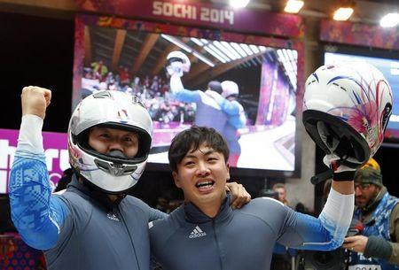 South Korea's pilot Won and Seo react after competing in the final run of the men's two-man bobsleigh competition at the 2014 Sochi Winter Olympics