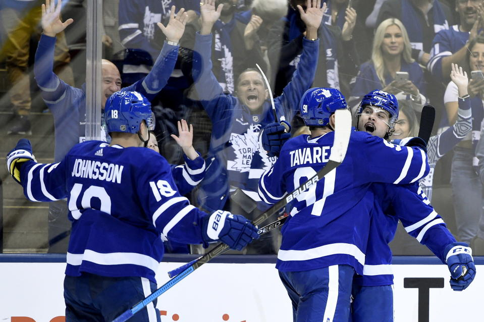 Toronto Maple Leafs center Auston Matthews (34) celebrates his goal with teammates John Tavares (91) and Andreas Johnsson (18) during the second period of an NHL hockey game against the Ottawa Senators, Wednesday, Oct. 2, 2019 in Toronto. (Nathan Denette/The Canadian Press via AP)