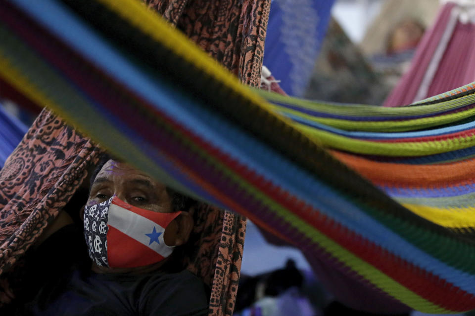 A passenger wears a mask to curb the spread of COVID-19, during a boat trip to the city of Breves, located in the island of Marajo, Para state, on the mouth of the Amazon river, Brazil, Thursday, Dec. 3, 2020. The city of Breves is a hub for river traffic, with boats coming from the cities of Belém, Manaus and Macapá, and a large concentration of passengers who largely do not respect social distancing guidelines to curb the spread of the new coronavirus. (AP Photo/Eraldo Peres)