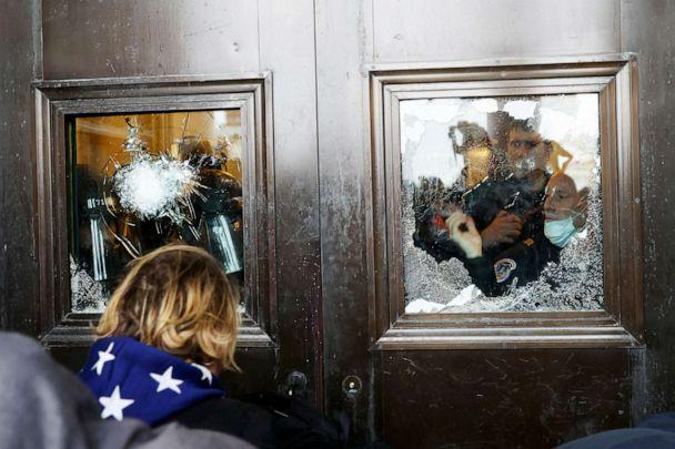 PHOTO: A Capitol police officer looks out of a broken window as protesters gather on the U.S. Capitol Building, Jan. 06, 2021.  (Tasos Katopodis/Getty Images, FILE)