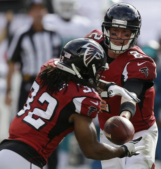 Atlanta Falcons quarterback Matt Ryan, right, hand the ball to Atlanta Falcons running back Jacquizz Rodgers (32) during the first half of an NFL football game against the Miami Dolphins, Sunday, Sept. 22, 2013, in Miami Gardens, Fla. (AP Photo/Lynne Sladky)