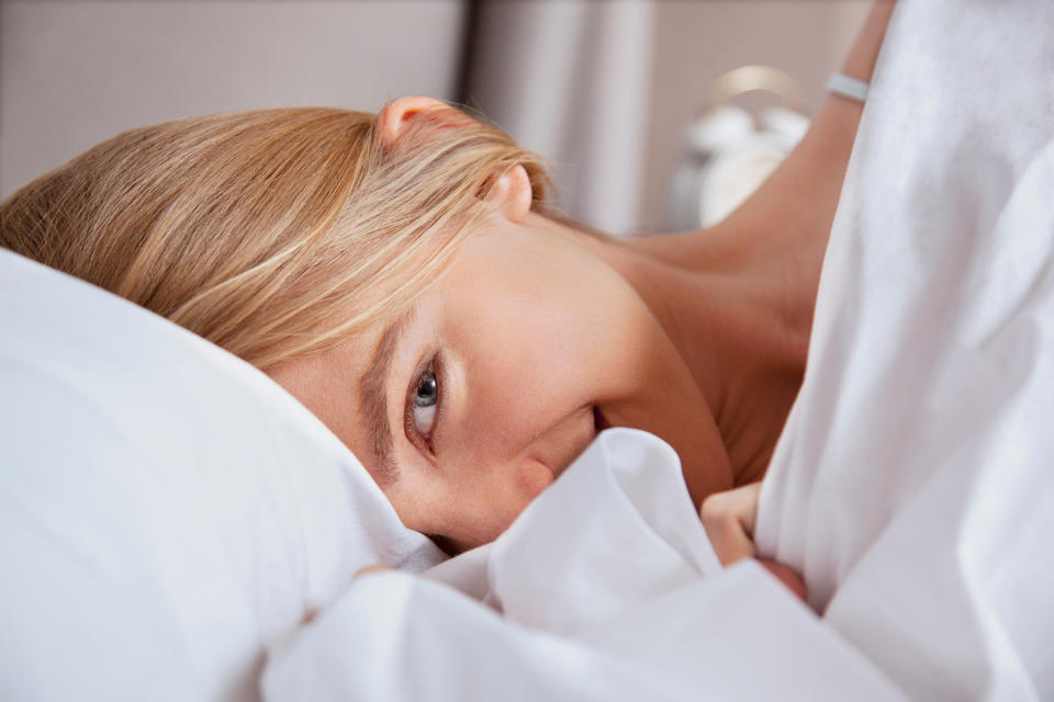 Woman looks cheeky in bed represents female masturbation