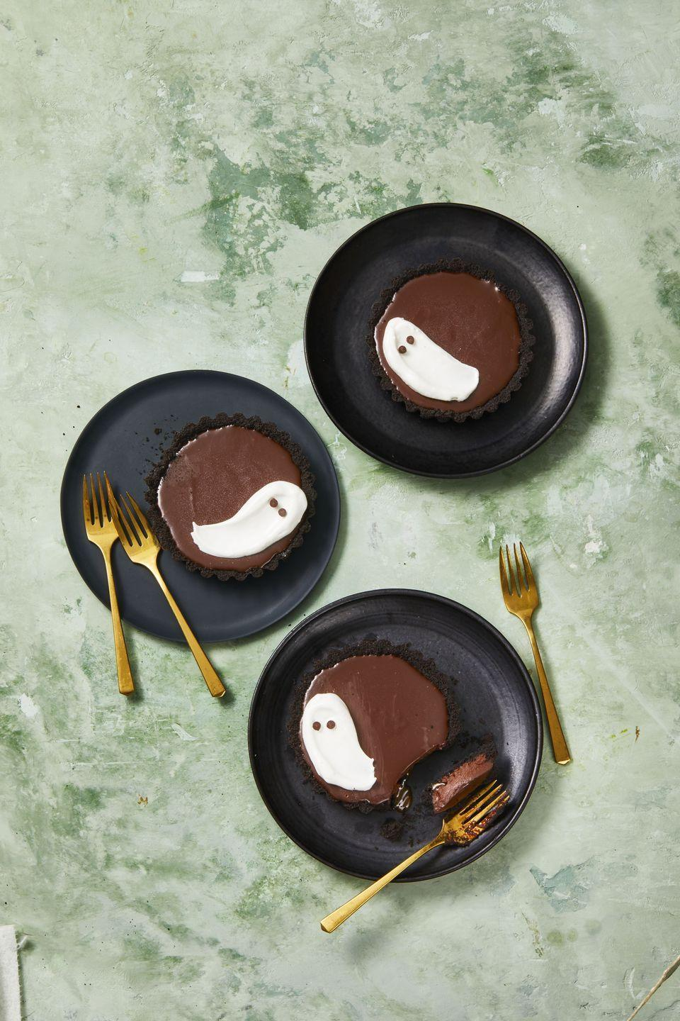 """<p>Decadent chocolate and caramel make this treat devilishly delicious while the meringue ghosts are frighteningly festive!</p><p><em><a href=""""https://www.goodhousekeeping.com/food-recipes/a34330877/meringue-ghost-tarts-recipe/"""" rel=""""nofollow noopener"""" target=""""_blank"""" data-ylk=""""slk:Get the recipe for Meringue Ghost Tarts »"""" class=""""link rapid-noclick-resp"""">Get the recipe for Meringue Ghost Tarts »</a></em></p>"""