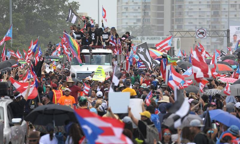 A truck carrying the singer Ricky Martin and rappers Residente and Bad Bunny joins with thousands of other people as they fill the Expreso Las Américas highway.