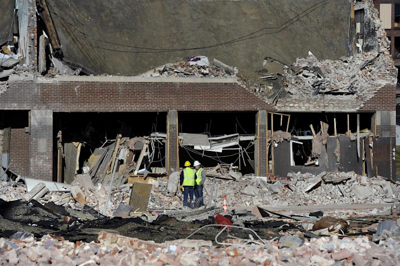 Inspectors stand in debris, Saturday, Nov. 24, 2012, at the site of a gas explosion that leveled a strip club in Springfield, Mass., on Friday evening. Investigators were trying to figure out what caused the blast where the multistory brick building housing Scores Gentleman's Club once stood. (AP Photo/Jessica Hill)