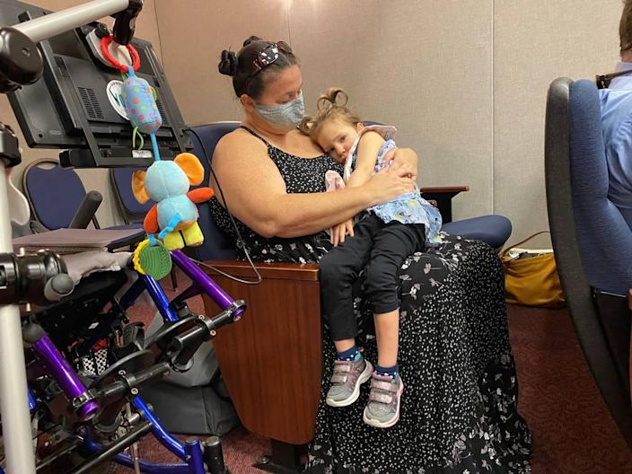 Jayme O'Connell, with her daughter Ivy, who is in the NICA program, at a legislative committee meeting in Tallahassee on Monday, said she is grateful for NICA but that it needs to be fixed.