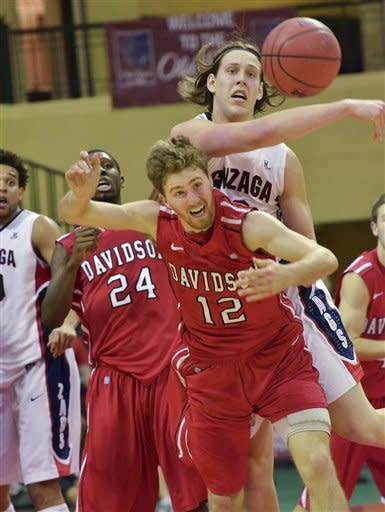 Gonzaga forward Kelly Olynyk goes for a loose ball against Davidson guard Nik Cochran (12) during the first half of an NCAA college basketball game at the Old Spice Classic in Kissimmee, Fla., Sunday, Nov. 25, 2012. (AP Photo/Roberto Gonzalez)