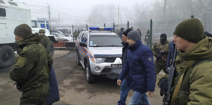 Ukrainian war prisoners escorted by Russia-backed separatist soldiers walk to be exchanged near the checkpoint Horlivka, eastern Ukraine, Sunday, Dec. 29, 2019. Ukrainian forces and Russia-backed rebels in the east have begun exchanging prisoners in a move aimed at ending their five-year-long war. (AP Photo/Alexei Alexandrov)