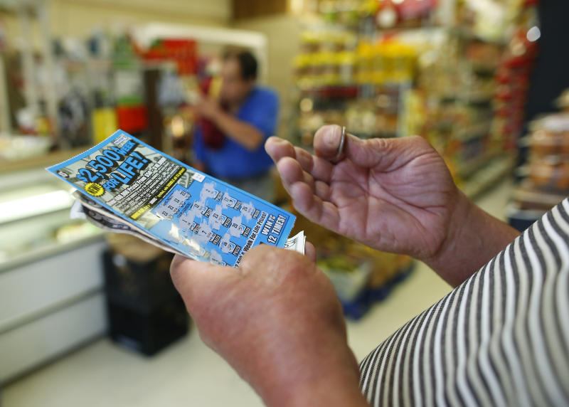 CHELSEA, MA - JUNE 4: A man scratches a lottery ticket at Tan-Thang Market on Broadway in Chelsea, Mass., June 4, 2014. (Photo by Jessica Rinaldi/The Boston Globe via Getty Images)