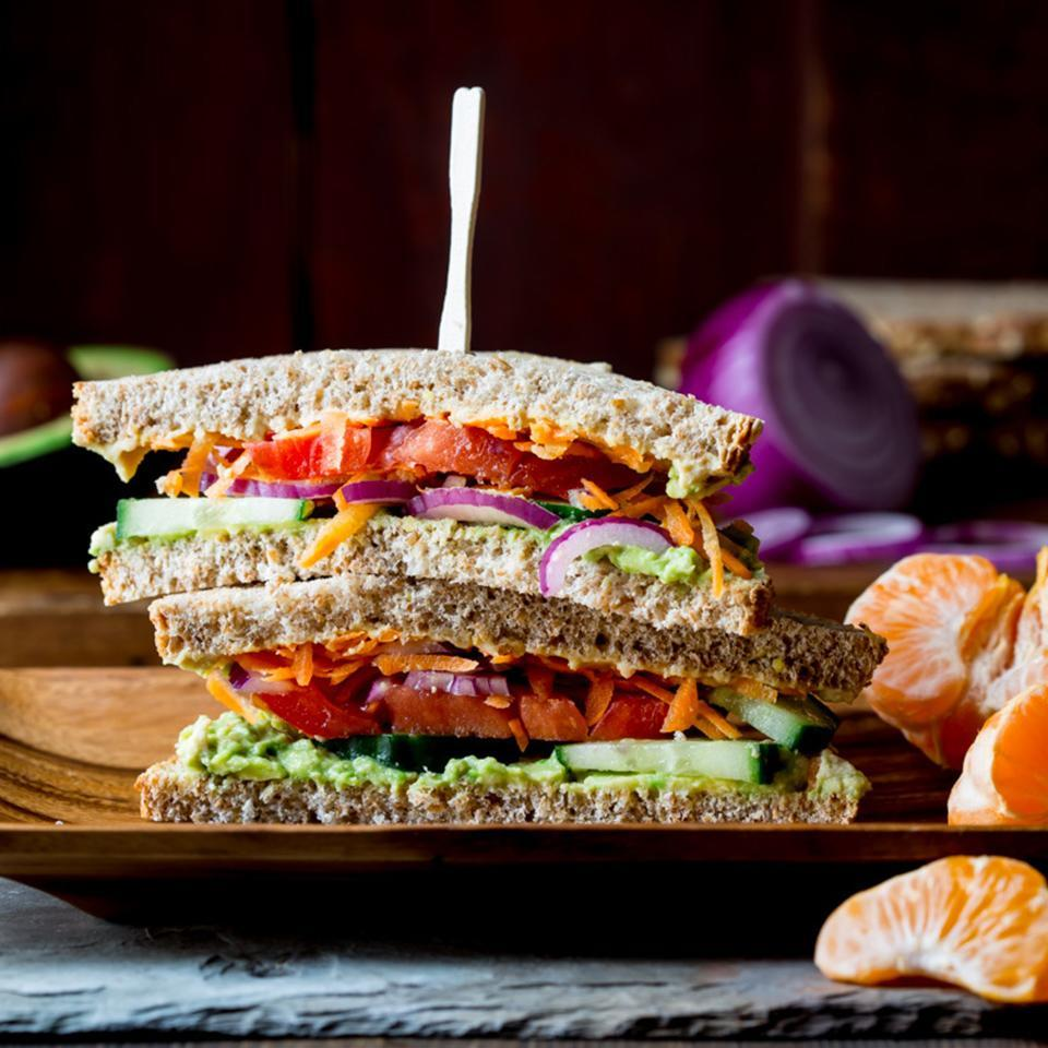 """<p>There's no chance of getting the afternoon munchies when you fuel up with this vegan veggie sandwich filled with fiber and healthy fats, plus fruit on the side. It'll keep you energized until dinner. Feel free to swap in your other favorite sandwich vegetables, sprouts or greens. <a href=""""https://www.eatingwell.com/recipe/259818/veggie-sandwich/"""" rel=""""nofollow noopener"""" target=""""_blank"""" data-ylk=""""slk:View Recipe"""" class=""""link rapid-noclick-resp"""">View Recipe</a></p>"""