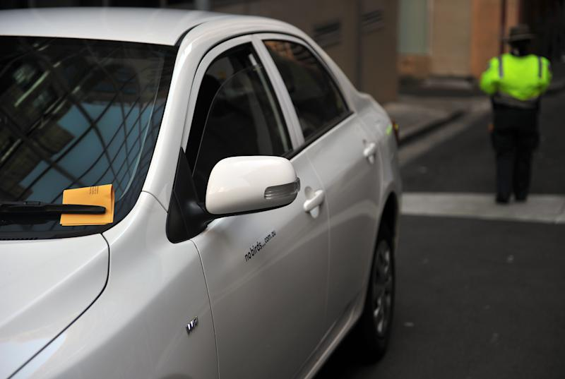A stock image of a car with a ticket under the windscreen wiper, and a parking officer in the background.