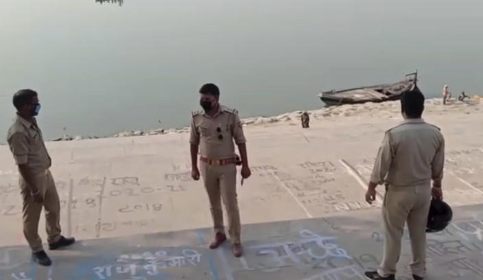 This frame grab from video provided by KK Productions shows police officials stand guard at the banks of the river where several bodies were found lying in Ghazipur district in Uttar Pradesh state India, Tuesday, May 11, 2021. Scores of dead bodies have been found floating down the Ganges River in eastern India amid a ferocious surge in coronavirus infections in the country, but authorities said Tuesday they haven't been able to determine the cause of death. Health officials working through the night Monday retrieved 71 bodies, officials in Bihar state said. (KK PRODUCTIONS via AP)